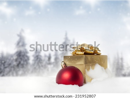 Christmas decorations and gift box in snow - firs in the background - stock photo