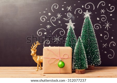 Christmas decorations and gift box over chalkboard background - stock photo