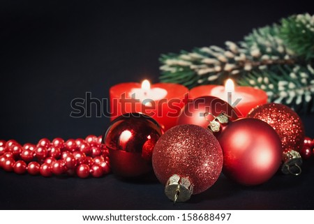 Christmas decorations, candles, fir branch on a black background - stock photo