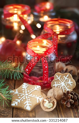 Christmas decorations. Candles in glass jars with fir and gingerbread cookies - stock photo