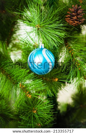 Christmas Decorations.  Christmas tree branch with a blue ball - stock photo