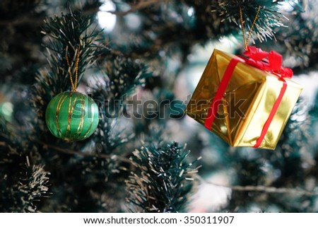 Christmas decorations focusing on green ball hanging on pine tree - stock photo