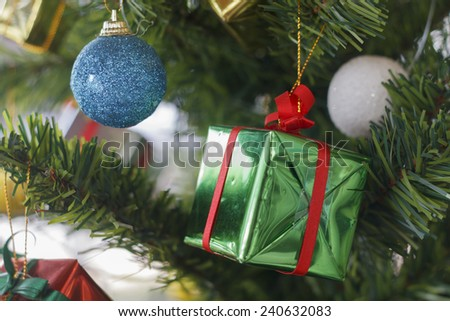 Christmas decorations gift box and Christmas balls hanging on pine tree  and Happy new year for background - stock photo