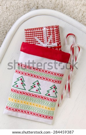Christmas decorations Gift box bag embroidered Christmas ornament traditional caramel on a white chair against a white carpet - stock photo