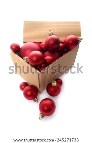 Christmas decorations: group of red Christmas balls in a kraft corrugated cardboard box, Christmas tree decorations, isolated on white background, wide-angle shot - stock photo