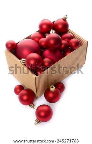 Christmas decorations: group of red Christmas balls in a kraft corrugated cardboard box, Christmas tree decorations, isolated on white background - stock photo