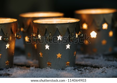 Christmas decorations: holey candle holders on snowy table, closeup - stock photo