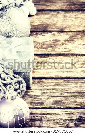Christmas decorations in silver tone on old wood background - stock photo