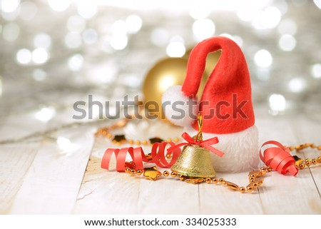Christmas decorations: Santa Claus hat and gold bell on the wooden table. - stock photo