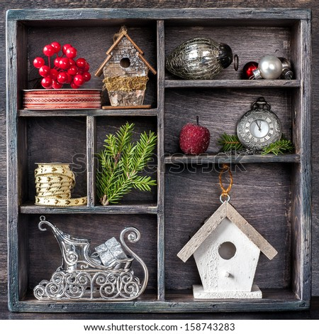 Christmas decorations set: antique clocks, birdhouse, Santa's sleigh and Christmas toys in an old wooden box - stock photo