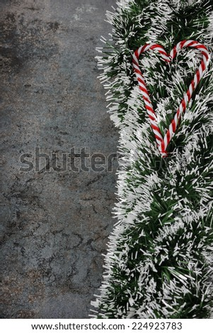 Christmas decorations - spruce tinsel and candy canes over dark background - stock photo