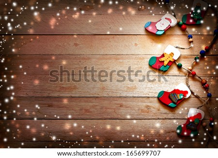 christmas decorations,stockings with Santa Claus, Christmas tree and gingerbread man on wooden background - stock photo