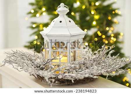 Christmas decorations with lantern and decorative wreath on fir tree background - stock photo