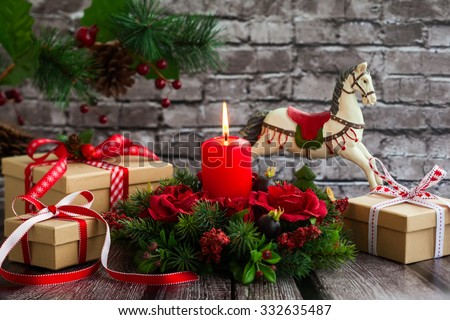Christmas decorations with red candle,gift boxes and rocking horse on  the old wooden table - stock photo