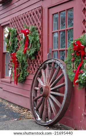 Christmas decorations with wagon wheel in lightly falling snow - stock photo
