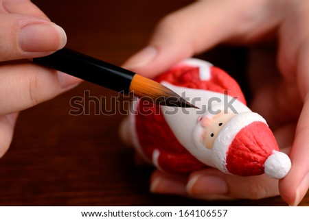Christmas decorations: woman hands with porcelain figurine of Santa, painting, making of Christmas decoration - stock photo