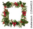 Christmas decorative border of holly, ivy, mistletoe, cedar leaf sprigs with pine cones and red baubles over white background. - stock photo