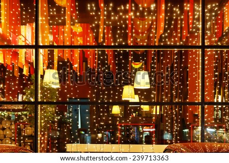Christmas decorative lights of restaurant window in night - stock photo