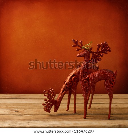 Christmas deer ornament on wooden table over red grunge background - stock photo