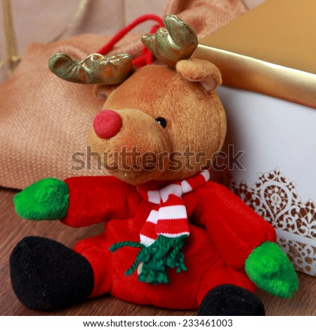 christmas deer toy over presents on Christmas/Handmade toy vintage Christmas deer sitting on light background with gift box - stock photo