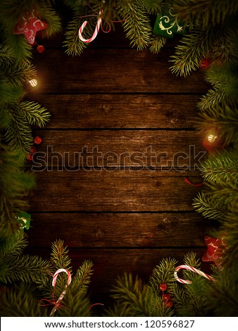 Christmas design - Merry Christmas. Xmas wreath card with with copyspace on wooden background. Christmas ornaments on wood with candy and ribbons. - stock photo