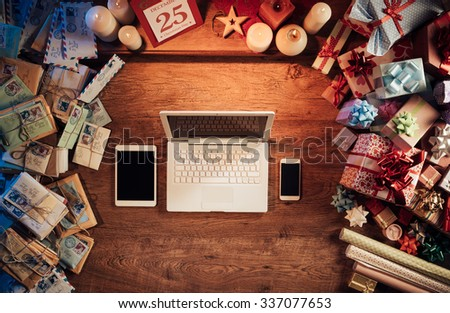 Christmas desktop with laptop, tablet and smart phone surrounded by gift boxes and letters, top view - stock photo