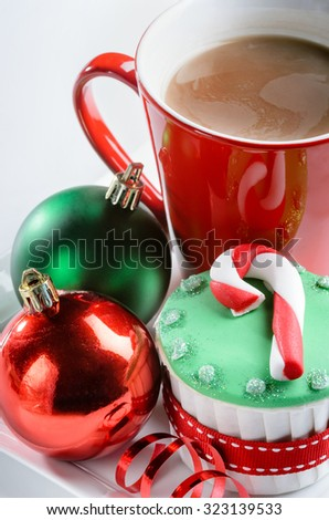 Christmas dessert cupcake with candy cane icing decoration red green xmas baubles ribbons and hot chocolate - stock photo