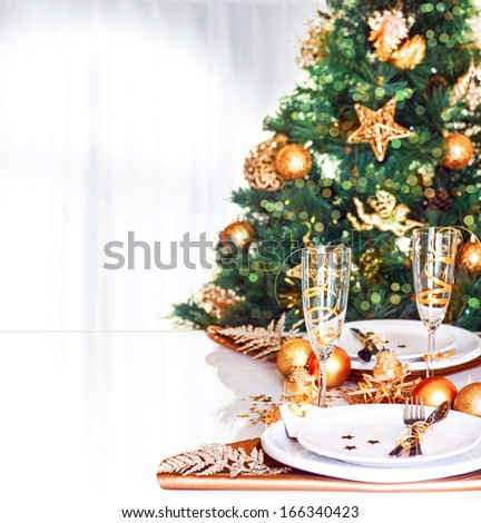 Christmas dinner decoration, fresh green fir tree decorated with shiny golden baubles, festive table setting, New Year celebration at home, greeting card with copy space  - stock photo