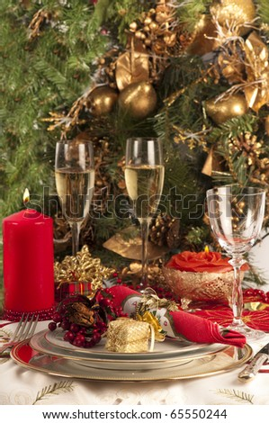 Christmas dinner place setting with Christmas table cloth,, plates, knife and fork, small presents, candles, christmas decorations champagne and wine glass, party - stock photo