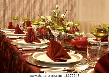 Christmas dinner table with flowers and red napkins - stock photo