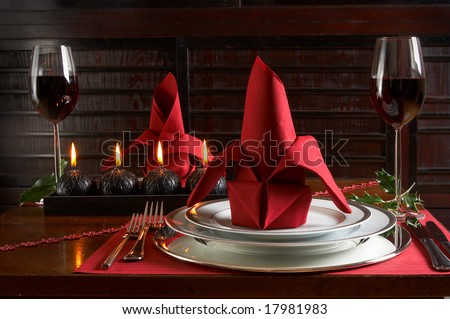 Christmas dinner table with red accents of placemats and napkins - stock photo
