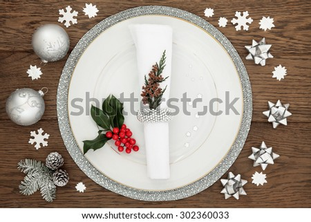 Christmas dinner time with plate, napkin, sparkling silver bauble decorations, holly and winter greenery over oak table background. - stock photo