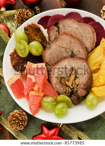 Christmas dinner turkey roulade with fruits and vegetables. Shallow dof. - stock photo