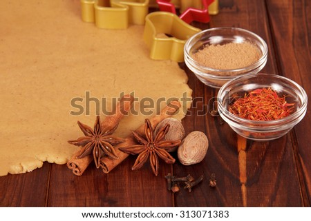 Christmas dough with cookie cutters, spices and nuts - stock photo