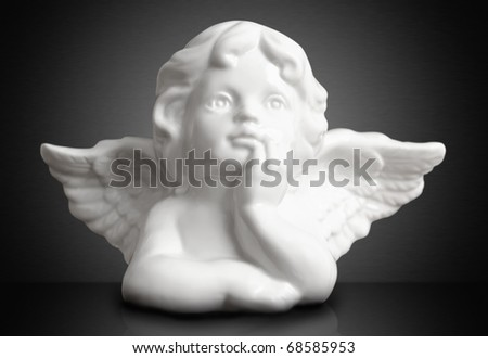 Christmas dreaming angel against black background. Small DOF, focus on eyes. - stock photo