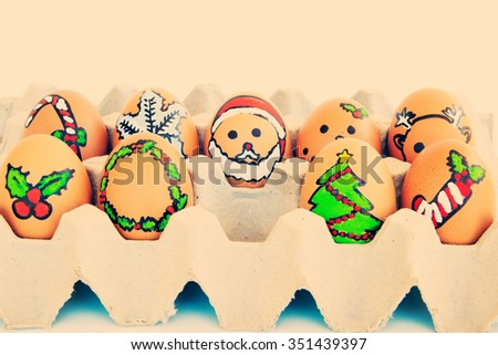 Christmas egg with faces drawn arranged in carton - stock photo