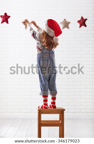 Christmas Eve! A small child hangs the stars in garland. - stock photo