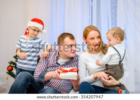 Christmas Family - Father, Mother and children opening Christmas gifts. - stock photo