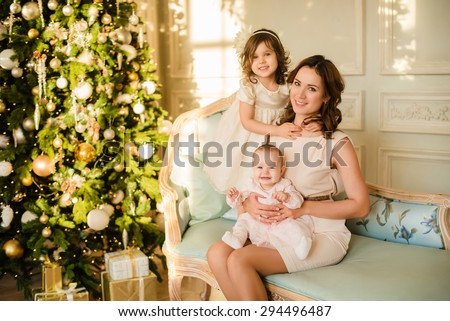 Christmas Family Portrait In Home Holiday Living Room, Kids and Baby Present Gift Box, House Decorating By Xmas Tree Candles Garland - stock photo