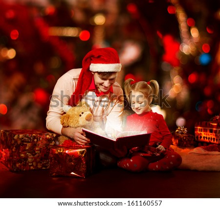 Christmas family reading book. Father and child opening magic fairy tale over red background. - stock photo