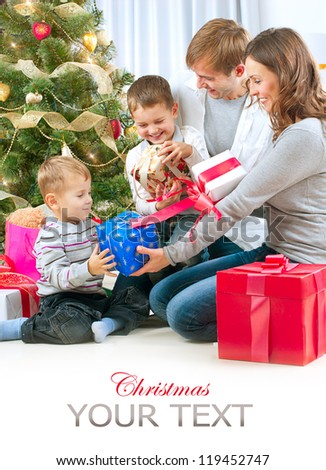 Christmas Family with Kids. Happy Family Opening Gift. Christmas tree - stock photo