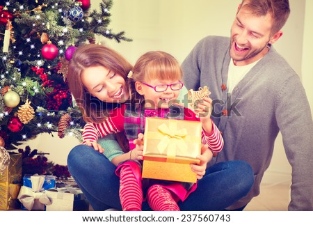 Christmas Family with little daughter opening Christmas gifts. Happy Smiling Parents and Child at Home Celebrating New Year. Christmas Tree. Christmas scene  - stock photo