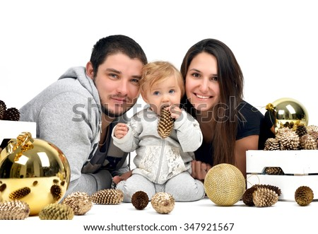 Christmas Family with small baby Kid and gold fir cones and balls decoration. Happy young Parents and Child at Home Celebrating New Year - stock photo