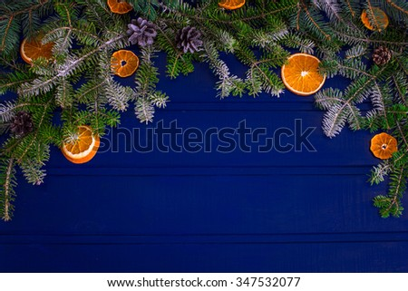 Christmas fir branches with cones in snow and dry orange slice, top view - stock photo