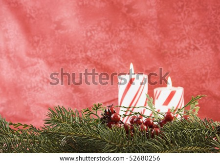 Christmas fir garland with holly berry accent, striped candle background and copyspace - stock photo