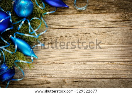Christmas fir tree branch with decorations on an old wooden plank, copy space for text, top view. - stock photo