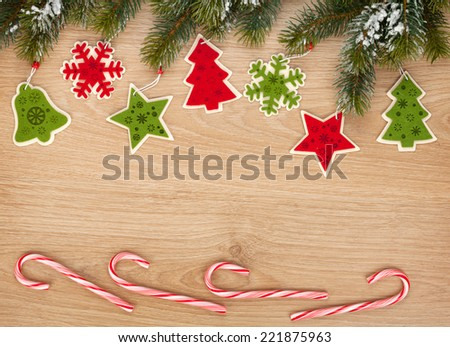 Christmas fir tree, candy cane and decor on wooden board with copy space - stock photo