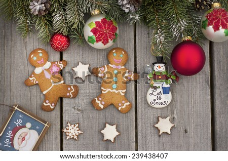 Christmas fir tree, ornaments and gingerbread men on the wooden texture - stock photo