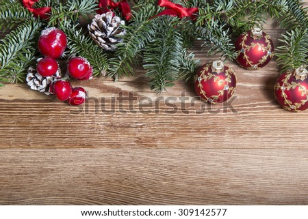 Christmas fir tree with baubles on rustic wooden board with copy space - stock photo