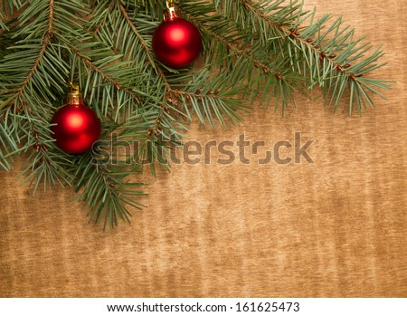 Christmas fir tree with christmas red ball on wooden background - stock photo